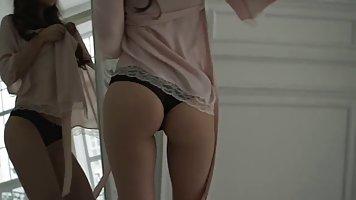 Девушка перед зеркалом показывает соло стриптиз и хвастается своими формами